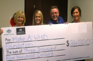 Staff holding up giant cheque for Make A Wish foundation