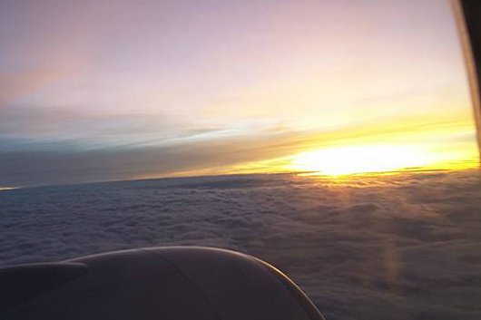 Sunset from the window of an airplane above the clouds.