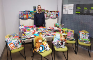 Paul Kaproulias standing in a DHS office. He is standing behind a table filled with colouring books. In front of the table are four chairs with various textas, soft toys, etc, on them. Behind him are cabinets with various boxed toys stacked on top of it.