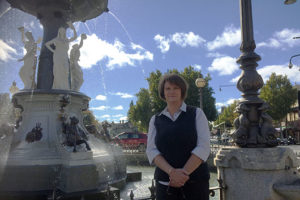 Sue Slattery standing outside in front of a large water fountain