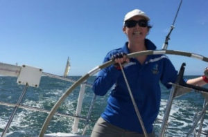 Sarah Twigger steering a boat and smiling.