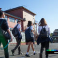 Five students in school uniform walking past a large red brick school.