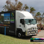 A Mobile Service Centre parked on the road at Airlie Beach. There are trees in the background, including one that has been uprooted.