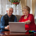 Two older people sitting on a couch focusing on a laptop.