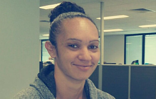 Photo of Kashia in the office, smiling at the camera.