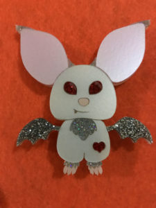 Brooch of a white craft bat with large pink ears, silver glittery wings, and red eyes - on an orange background.