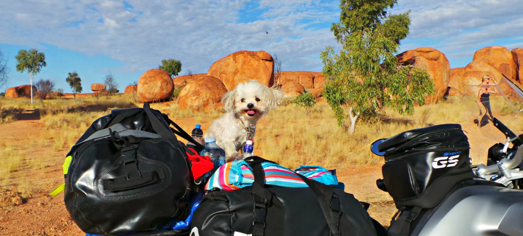 Chloe seated on the back of a motorbike in the outback of Alice Springs.