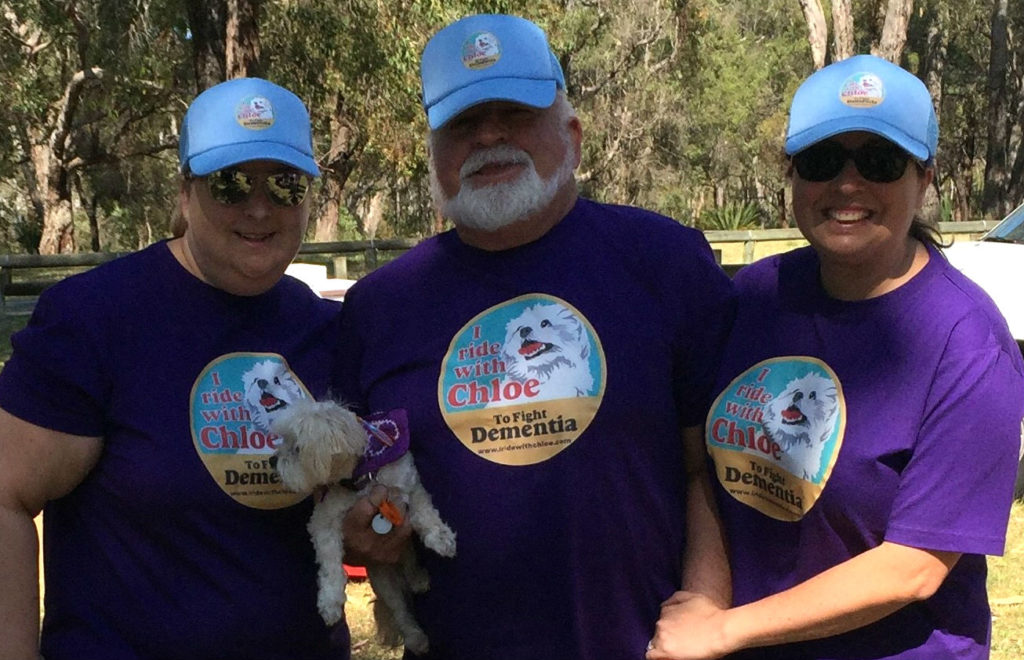 L-R: Heidi, her father Ken (holding Chloe) and sister Kylee on the Memory Walk & Jog. All are wearing purple t-shirts with the 'I Ride With Chloe To Fight Dementia' logo, and are smiling at the camera.