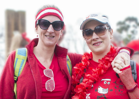 Picture of Veronica and her sister wearing sunglasses and dressed in red. They are both looking at the camera and smiling.