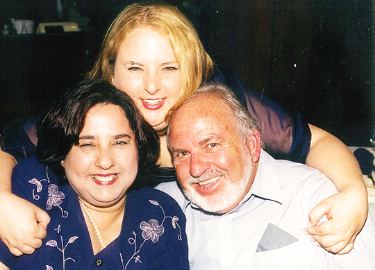 Photo of Heidi with her arms around her parents Sue and Ken. They are all facing the camera and smiling.
