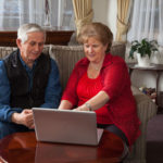 man and woman are sitting with laptop