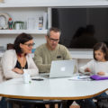 Parents and younger child sitting at table with laptop